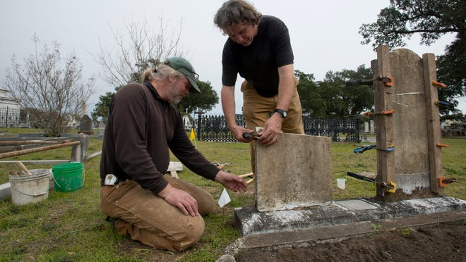 Martin Johnson, left, and Karl Munson, right, of New England-based Monument Conservation Collaborative, work on restoring one of several broken headstones in St. Michael's Cemetery in downtown Pensacola March 2, 2015.