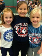Three Bridges School first graders Bridget Kelliher, Annalisa Dotro and Abigail Lagola  show respect for their school by wearing school spirit T-shirts during the Week of Respect.