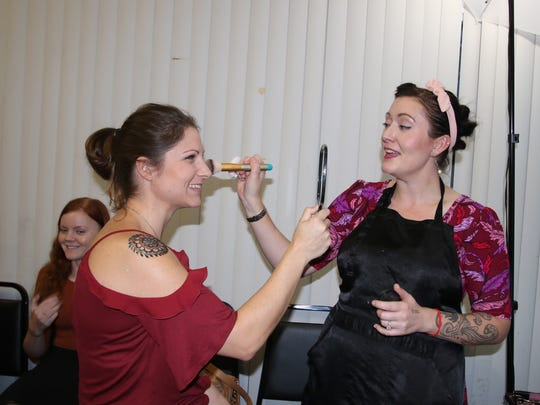 Makeup artist Joah May, right, gives Rachael Lacelle