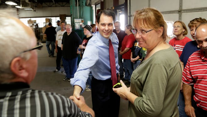 In this Sept. 23, 2014 photo Republican Wisconsin Gov. Scott Walker talks with employees as he campaigns for re-election at a manufacturing company in Racine. The airwaves and campaign appearances in the closely contested governor's race here are bristling with arguments designed to sway opinions before Election Day. But for nearly everyone in Wisconsin, the only issue is Scott Walker. And almost every voter already knows whether they love him or hate him.