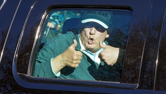 President Donald Trump gives two thumbs up to supporters as he departs after playing golf at the Trump National Golf Club in Sterling Va., Sunday Nov. 8, 2020.