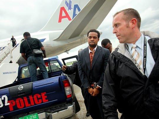 Mesac Damas is led out of the Central Department of Judicial Policing in Port-Au-Prince, Haiti, to be returned to Florida on an American Airlines flight on Tuesday, Sept. 22, 2009. Damas confessed to reporters that he killed his wife and five children in Naples and that he wants the death penalty and to be buried next to them. Lexey Swall/Staff