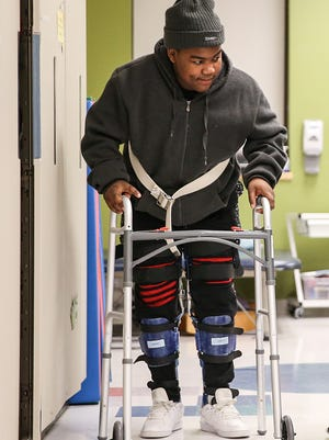 Ty-Juan Preer walks with leg braces and a walker during a physical therapy session at Riley Children's Hospital in Indianapolis, Friday, March 30, 2018.