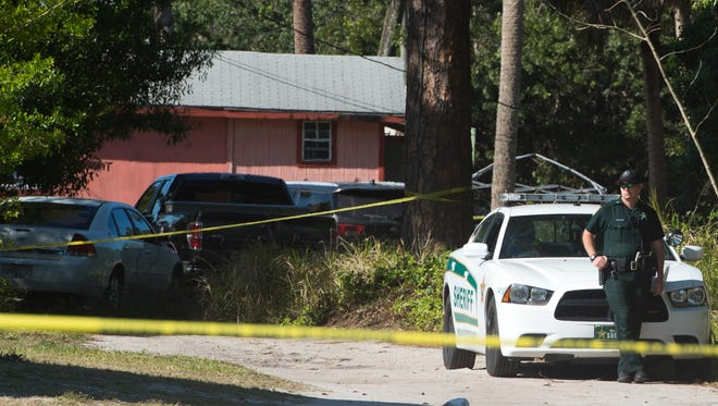 An Indian River County Sheriff's deputy secures the area around a known drug house off 45th Street, between 34th and 36th avenues on Sunday, March 19, 2017, in Gifford. Authorities were attempting to enforce a search warrant early Sunday morning when shots were fired from inside the house. Alteria Woods, 21, was killed in the exchange of gunfire. Andrew Coffee IV, 23, is in the Indian River County Jail on charges of attempted murder of law enforcement officers. Coffee's father, Andrew Coffee III, 37, also was arrested and is in jail under multiple drug charges.