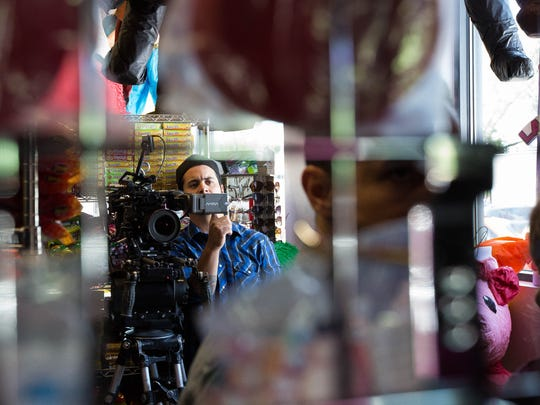 "Michael Garcia, director of photography, looks over a scene during filming of ""All The World is Asleep"" inside Paleteria La Reyna Michoacana, on Wednesday, May 23, 2018."