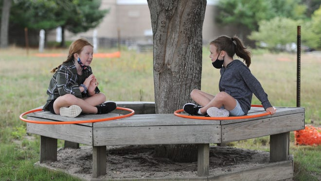 Harwich Elementary School second graders Maeve Casey, left, and Camille Thonus, both 7, spend some of their mask break time catching up while maintaining distance. Students returned to the school Monday morning with new safety protocols in place.