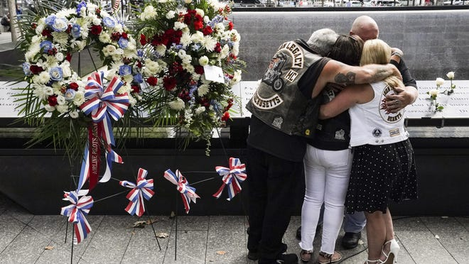 Mourners hug Friday beside the names of the deceased Jesus Sanchez and Marianne MacFarlane at the National September 11 Memorial and Museum in New York.