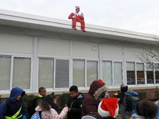 Tom Braddock, principal at Evergreen Avenue School in Woodbury, greeted his students on the last day of school before the holiday break. He dressed as Santa's spy - the infamous Elf on the Shelf.