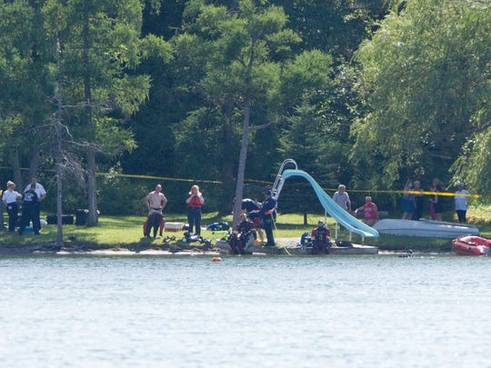 The Livingston County Sheriff's Dive Team searches for an 18-year-old Chesterfield Township boy who went under the water on Hartland's Handy Lake Monday afternoon. His body was later recovered drowned.