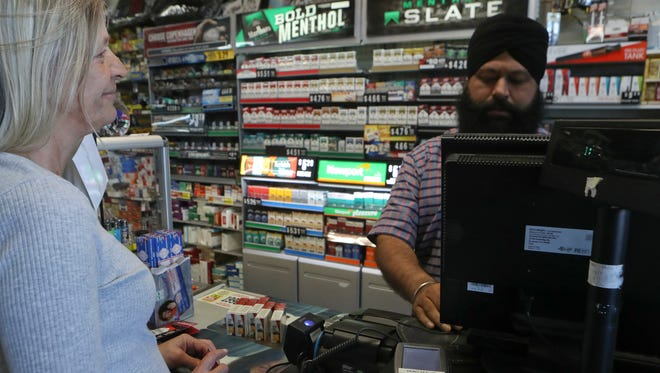 Sherri Howard, left, of Round Mountain buys five packs of cigarettes from Raj Singh Kahlon at Discount Tobacco on Friday in Redding. Taxes on cigarettes will go up $2 a pack on April 1.