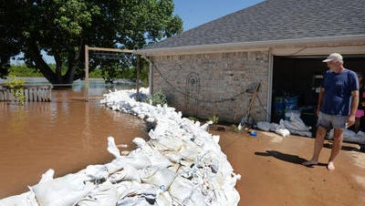 Bill Carrier looks at the sandbag wall that separates his house from floodwater Wednesday morning, June 10, 2015, in Bossier City, Louisiana. Carrier and his wife with help from their friends have managed to keep the water from entering their house for the several days. Today the water has gone down about an inch according to their marker.