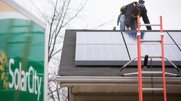 A SolarCity employee installs a solar panel.
