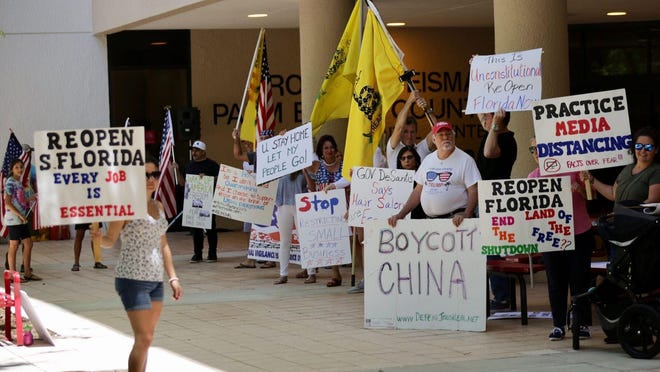 Protesters against the mandatory shutdown of non-essential businesses demonstrate outside the Palm Beach County Governmental Center Tuesday before the county commission meeting.