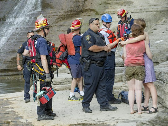 Sgt. Michael Nelson of the Ithaca Police Department, center, talks to a 16-year-old girl and her mother, right, after the Ithaca Fire Department rescued the teenager and a male teenager off the south cliff wall of the gorge Tuesday afternoon.