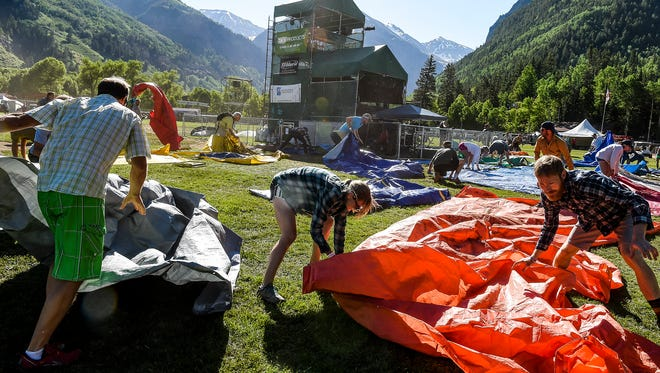 """Festival attendees rush their tarps onto the field to claim a good spot as they participated in the """"tarp run,"""" Friday, June 19, 2015, in Telluride, CO. The """"tarp run"""" is a tradition of the Bluegrass Festival, with many people waiting overnight in line."""