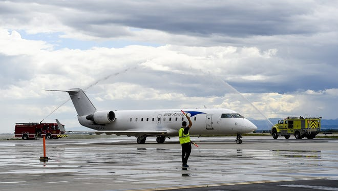 Fire trucks shoot streams of water over the first Elite Airways flight from the Chicago Rockford International Airport to Northern Colorado Regional Airport, formerly the Fort Collins-Loveland Municipal Airport Thursday, Aug. 27, 2015.