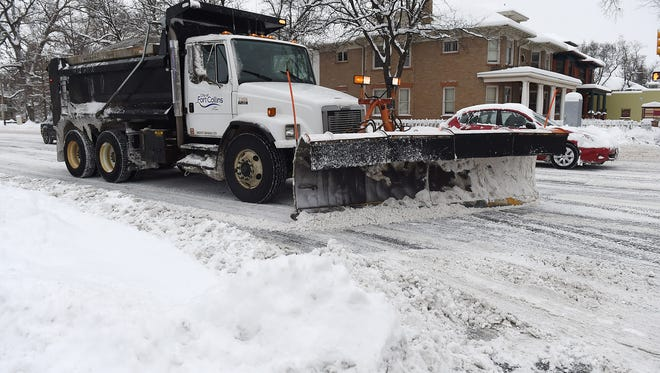 A city plow scrapes snow from a Fort Collins street Tuesday. Residents gave the city's decision to plow all residential streets mixed reviews.