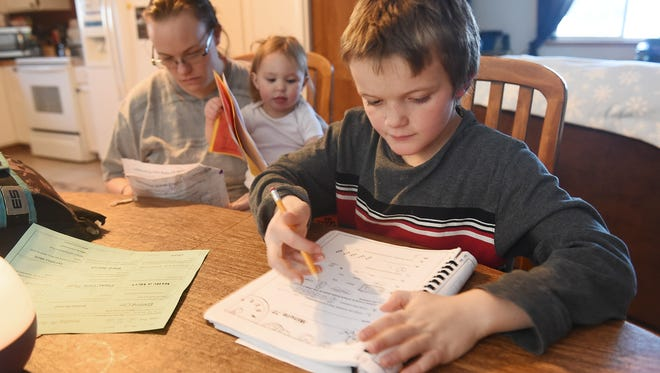 Jaden Riggs, 8, does homework with his mom, Jenny Cross, and sister Aspen Dawson, 16 mos., on Wednesday, February 3, 2016. Jaden is a second grader at McGraw Elementary and his mother said she thinks he has about the right amount of homework.