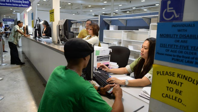 In this file photo, income tax specialist Joyce Canete assists James Naputi at the tax counter at the Department of Revenue and Taxation.