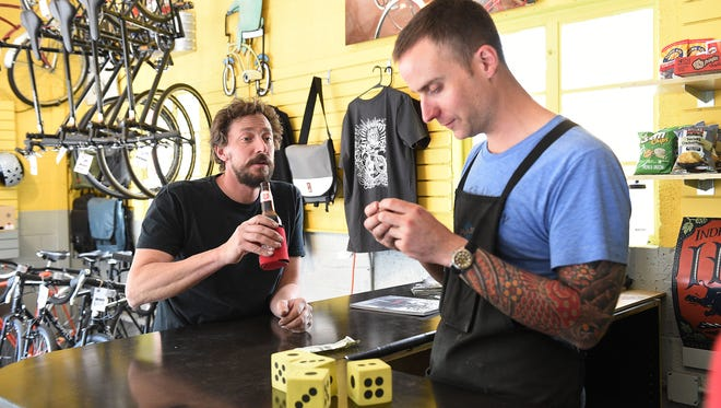 Nathan Hope has a Lone Star beer at Brave New Wheel while owner Mike Woodward tries to decipher the puzzle inside the cap on Tuesday, May 10, 2016.