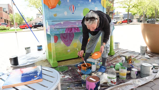 Gale Whitman paints the first piano of the season for Pianos About Town at Old Town Square on Thursday, May 19, 2016.