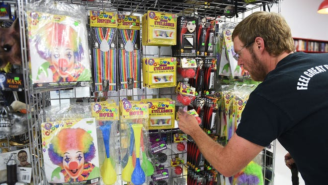 Store manager Eric Bowers arranges new costume items at arc Thrift Store on Friday in Fort Collins.