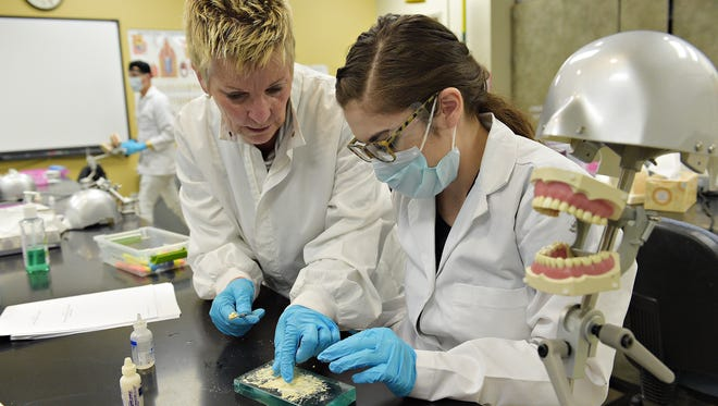 Nicci Edwards shows Veronica Valdez how to mix a cement in a dental assisting lab at Front Range Community College on Wednesday, February 8, 2017. Valdez was at risk of dropping out of high school until she started the Opportunities Unlimited program.