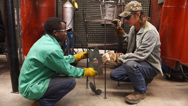 Guy Seguele, left, works on a project in welding class with Jacob Grudle at Front Range Community College on Monday, September 19, 2016. Seguele survived a civil war in Africa and was a 2016 First Class Scholar.