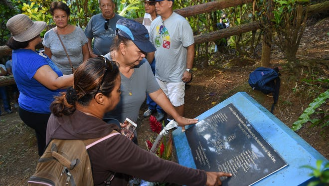 Visitors look for names on a memorial plaque at the Tinta Massacre Site in Merizo on July 15, 2017.