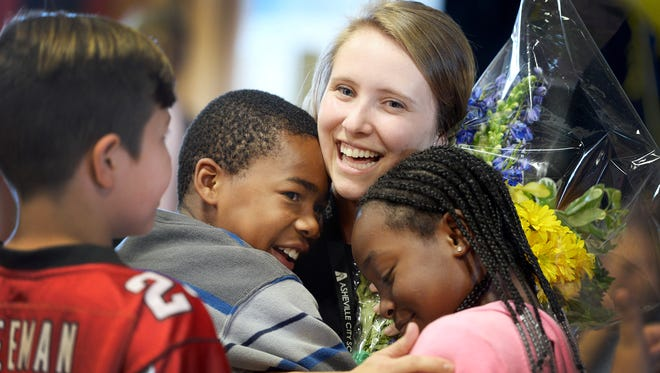 Rebecca Wertheim, a second grade teacher at Claxton Elementary, receives a hug from former students De'Aijai Ray, left, and Siyuna Boyd after a surprise announcement that she received Asheville City Schools' teacher of the year award September 18, 2017.
