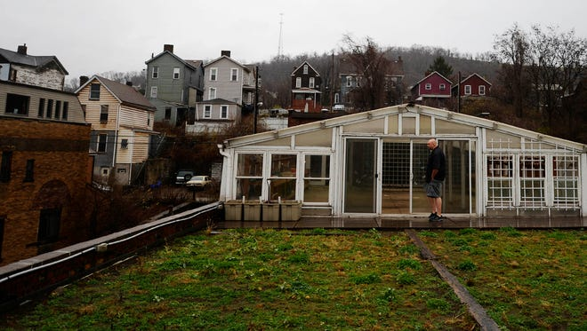 The borough of Braddock, Pa., is seen behind a green house on the roof of John Fetterman's home, a former car dealership, Tuesday, December 22, 2015. Fetterman grew up in Springettsbury Township, and has been mayor of Braddock since 2005..