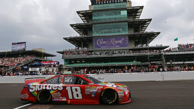 Sprint Cup Series driver Kyle Busch (18) crosses the finish line to become the winner of the Jeff Kyle Brickyard 400, Indianapolis Motor Speedway, Sunday, July 26, 2015, Indianapolis, Ind.