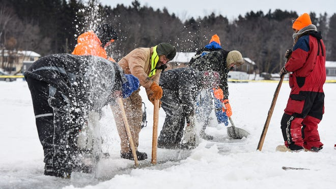 Volunteers work with chainsaws and shovels to clear around the the edge of a spinning ice carousel on Green Prairie Fish Lake on Jan. 6, 2018  near Camp Ripley.