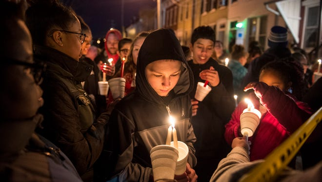 Walnut Street residents light candles Friday, March 23, 2018, at a neighborhood-organized vigil for Ivan Flanscha and Zachary Anthony, two York City firefighters who died in a building collapse nearby on Thursday. Assistant chief Greg Altland and firefighter Erik Swanson sustained injuries in the same collapse.