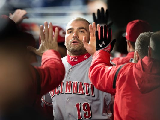 Cincinnati Reds' Joey Votto is congratulated in the dugout after scoring during the fourth inning of a baseball game against the Philadelphia Phillies, Wednesday, April 11, 2018, in Philadelphia. (AP Photo/Laurence Kesterson)