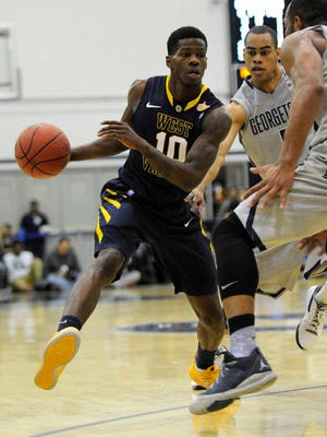 West Virginia guard Eron Harris (10) dribbles against Georgetown guard Markel Starks, center, and Jabril Trawick (55) during the first half of an NCAA college NIT tournament first round basketball game, Tuesday, March 18, 2014, in Washington. (AP Photo/Nick Wass)