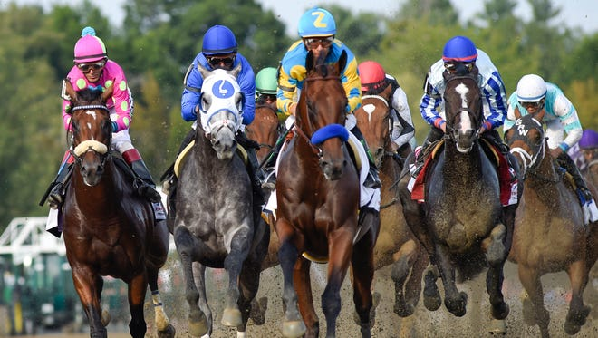 Triple Crown winner American Pharoah, center, with jockey Victor Espinoza, leads the field into the first turn during the Travers Stakes horse race at Saratoga Race Course in Saratoga Springs, N.Y., Saturday, Aug. 29, 2015. (AP Photo/Hans Pennink)