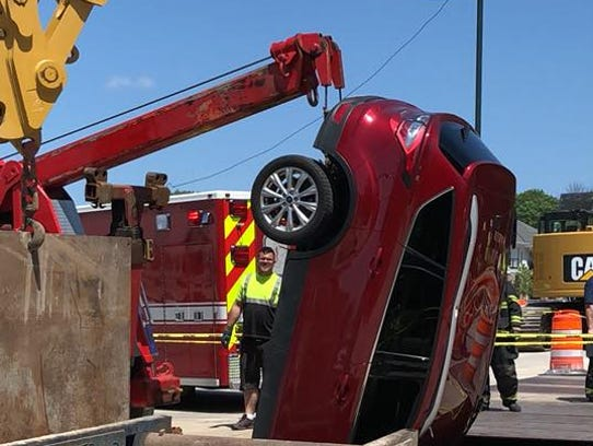 A crane lifts an SUV out of a trench near the intersection