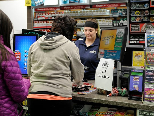 Anxious players purchase tickets for the $1.5 Powerball drawing at Friendship Food Store/Marathon gas station on E. Perry St. on Wednesday evening