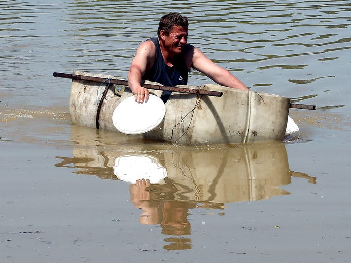 A man uses plates to paddle his makeshift raft away from his flooded home on May 22 in Brcko, Bosnia and Herzegovina. A state of emergency has been declared due to severe flooding caused by heavy rainfall.