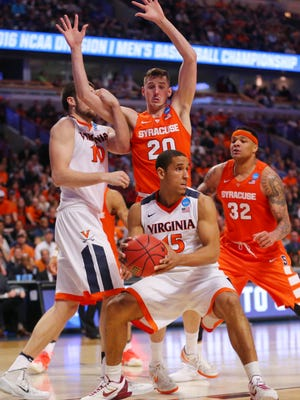 Virginia Cavaliers guard Malcolm Brogdon (15) controls the ball as center Mike Tobey (10) grabs the arm of Syracuse Orange forward Tyler Lydon (20) during the second half in the championship game of the midwest regional of the NCAA tournament at the United Center.