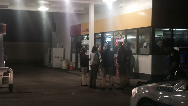 Investigators at the Shell station Wednesday night.