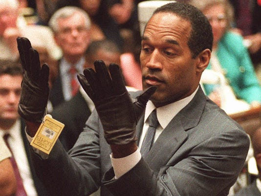 "O.J. Simpson holds up his hands before the jury after putting on a new pair of gloves similar to the infamous ""bloody gloves"""