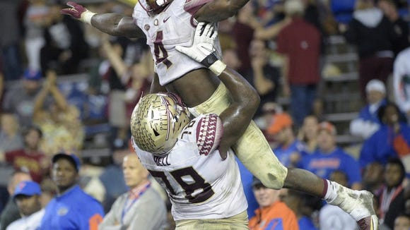 Florida State running back Dalvin Cook, top,  is congratulated by offensive lineman Wilson Bell after a 29-yard touchdown run against Florida in 2015.