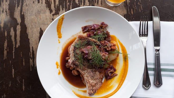 Bone-in Berkshire pork chop is served with baked beans, smoked sausage, cippolini onions, gold barbecue sauce and bacon-braised red cabbage.