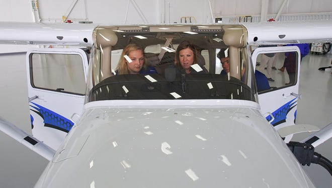Elizabeth Keller, left, and Harry Arcamudi, right, receive instructions about the Cessna Skyhawk 172's cockpit features from Textron Aviation flight instructor Chelsea Carlin in the company's Flight Operations building hangar April 12 in Wichita, Kan. Keller and Arcamudi helped fly the plane back to Murfreesboro.