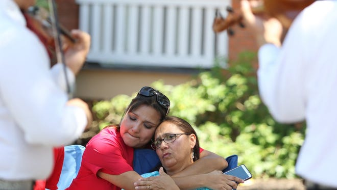 Audrey Hinojosa (left) hugs her mother Amanda Sanchez (right) while Mariachi Mexicanisimo performs at the Mother's Day Celebration presented by Driscoll Health Plan at Heritage Park on Sunday, May 3, 2015.
