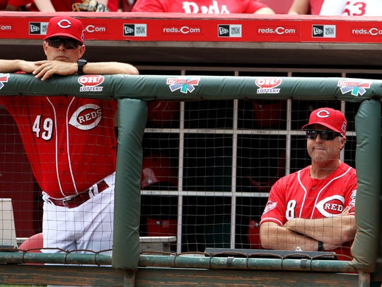 Reds bench coach Jay Bell, left, and manager Bryan Price watch as their team falls 6-4 to the Rockies at Great American Ball Park on Wednesday.