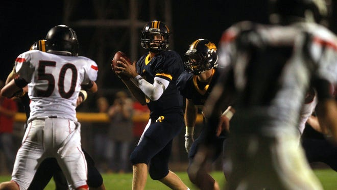 Iowa City Regina quarterback Drew Cook, center, for an open receiver during the Regals' game against Highland of Riverside.