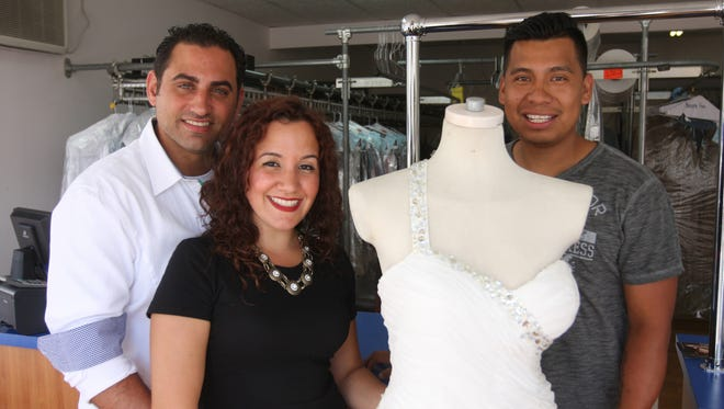 Michael, left, and Nicole Pagliaro pose with her wedding dress at the South Beach Dry Cleaners with owner Hector Pacheco in the Staten Island borough of New York.